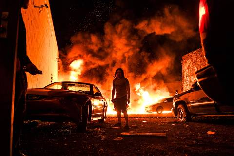 TOPSHOT - A man tries to toe away a car in a safe zone as the other car catches fire in a local parking garage on May 29, 2020 in Minneapolis, Minnesota, during a protest over the death of George Floyd, an unarmed black man, who died after a police officer kneeled on his neck for several minutes. - The Minneapolis police officer accused of killing a handcuffed African-American man was charged with murder on May 29, but the move failed to quell surging anger as tense protests erupted in cities across the nation. (Photo by CHANDAN KHANNA / AFP)