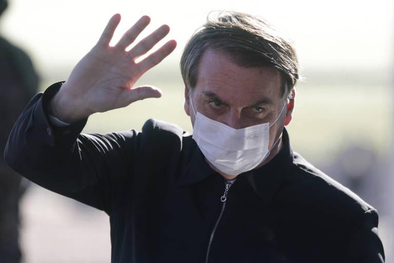 Presidente de máscara e acenando com a mão direita