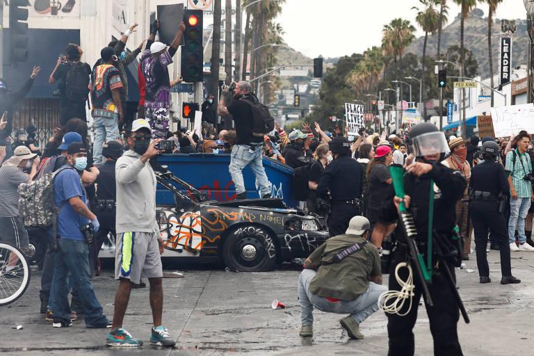 Manifestantes em cima de carro da polícia incendiado durante protesto em Los Angeles