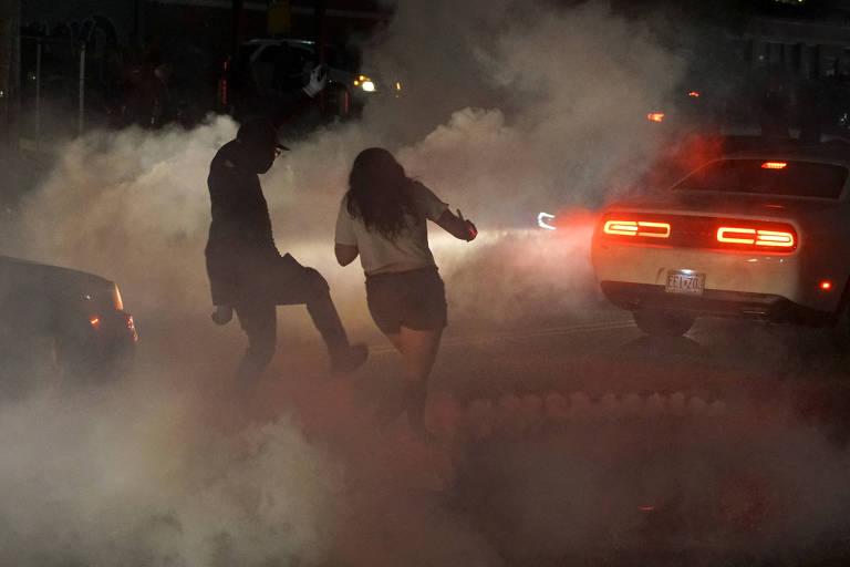 Pessoas tentam chutar para longe bomba de gás lacrimogêneo