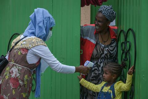Health Extension workers of the Ministry of Health measure the tempreature of a girl during a door to door screening to curb the spread of the COVID-19 coronavirus in Addis Ababa, Ethiopia, on April 20, 2020. (Photo by Michael Tewelde / AFP)