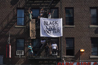 Onlookers hang signs from a building's fire escape as demonstrators crowd the nearby intersection at Ocean Avenue and Parkside Avenue in Brooklyn, as they protest the death of George Floyd and police brutality, on Saturday, May 30, 2020. (Chang W. Lee/The New York Times)