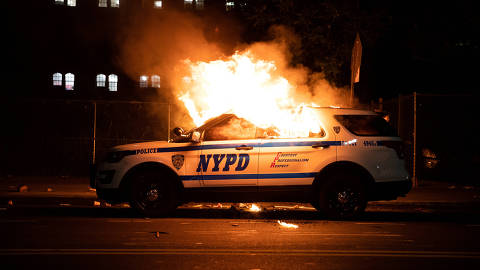 A NYPD police car is set on fire as protesters clash with police during a march against the death in Minneapolis police custody of George Floyd, in the Brooklyn borough of New York City, U.S., May 30, 2020. Picture taken May 30, 2020. REUTERS/Jeenah Moon     TPX IMAGES OF THE DAY ORG XMIT: PPP-JNM 304