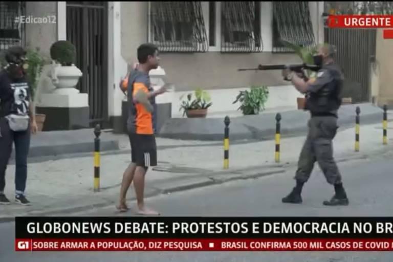 Policial aponta fuzil a homem durante os protestos em frente ao Palácio Guanabara