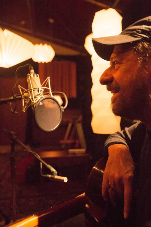 O cantor João Bosco de boné olhando para microfone em estúdio