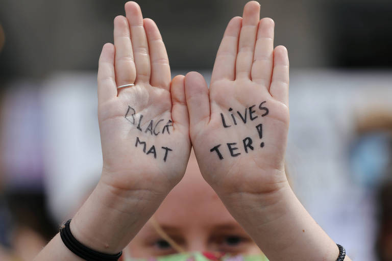 Manifestante com mensagem escrita nas mãos em protesto contra a morte de George Floyd