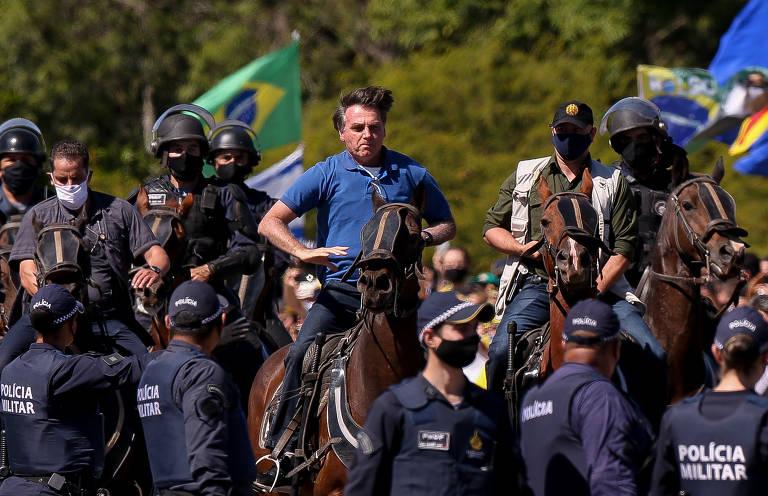 Bolsonaro galopa em cavalo marrom rodeado pela cavalaria da polícia militar