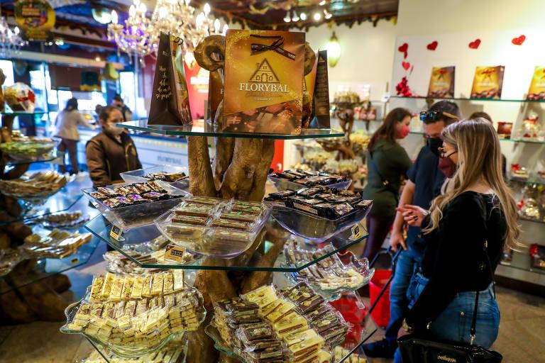 Pessoas em loja de chocolates, com máscara