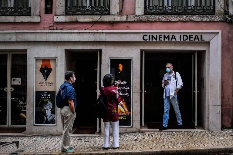 Um casal olha para um homem saindo da porta do cinema. Todos usam máscara. A calçada, de ladrilhos, é típica de Lisboa