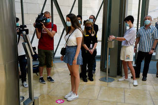 A visitor has her temperature taken at the Guggenheim Museum on the day it reopens its doors following a three-month closure, amid the coronavirus disease (COVID-19) outbreak, in Bilbao