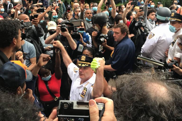 Policial se ajoelha com manifestantes do lado de fora do Washington Square Park