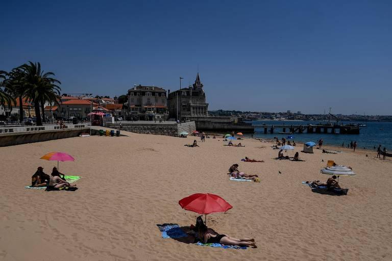 Pessoal tomam sol em praia de Cascais, em Portugal