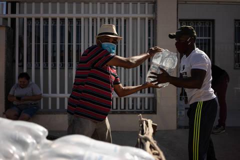 RIO DE JANEIRO,RJ - 30/05/2020 -** ESPECIAL** CORONAV�RUS - Distribuição de doações em Guaratiba, Zona Oeste do Rio de Janeiro, realizado pelo CENTRO CULTURAL LUTANDO POR QUEM PRECISA. José Roberto, 56 anos, ajuda a carregar doações em sua carroça. (Foto: Tércio Teixeira /Folhapress)