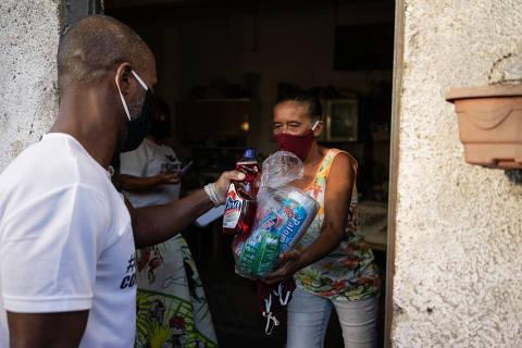 RIO DE JANEIRO,RJ - 28/05/2020 -** ESPECIAL** CORONAV�RUS - Distribuição de doações em Guaratiba, Zona Oeste do Rio de Janeiro, realizado pelo CENTRO CULTURAL LUTANDO POR QUEM PRECISA. Raimunda Lourenço dos  Santos, 65 anos com suas bisnetas, recebe doações feita pelo Centro Cultural. (Foto: Tércio Teixeira /Folhapress)