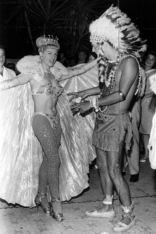 homem fantasiado de índio e mulher de biquini, coroa e manto