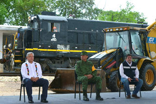 Mexico's President Andres Manuel Lopez Obrador sits next to Mexico's Defense Secretary Luis Cresencio Sandoval during the start of the third section of the construction of the Mayan Train railroad project, in Maxcanu