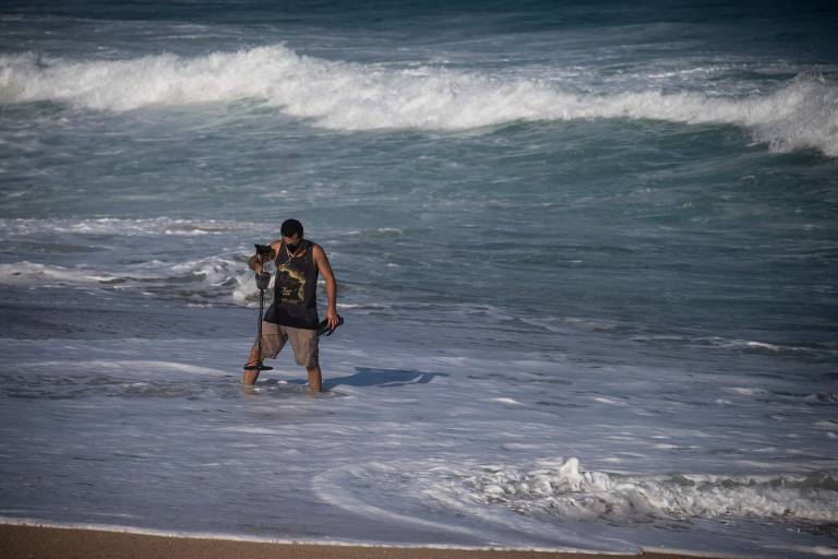 homem vasculha o mar com instrumento que detecta metais em praia