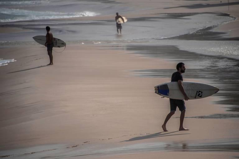 tres homens com pranchas na areia perto do mar