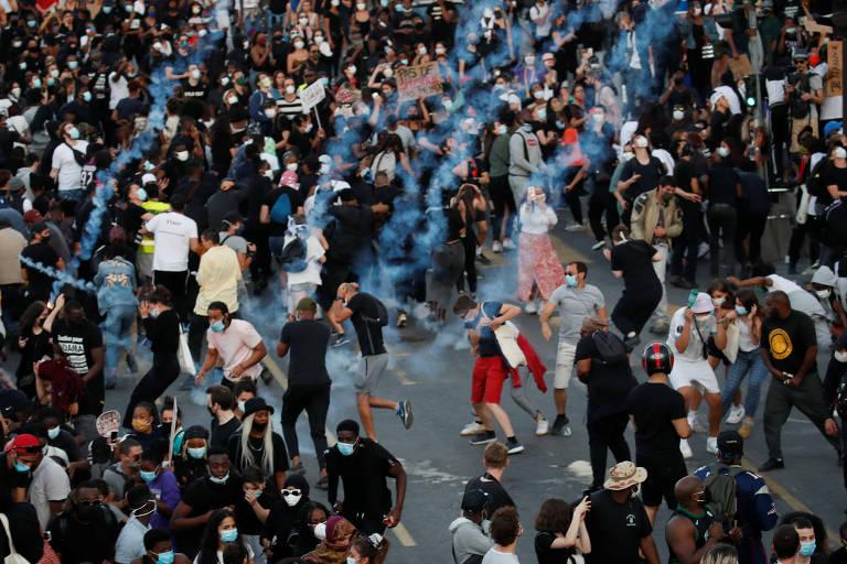 Manifestantes correm após a polícia disparar bombas de gás lacrimogêneo durante manifestação em Paris