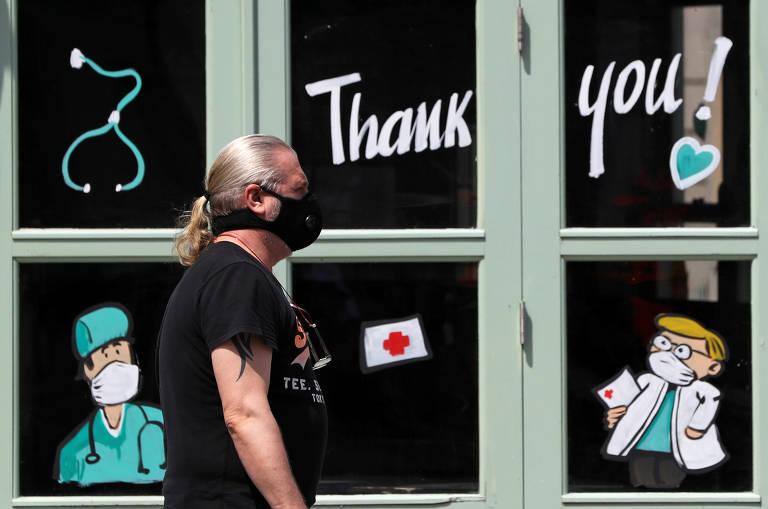 Homem usando máscara de proteção caminha em frente a um bar com desenhos que fazem homenagem aos profissionais da saúde, na cidade de Bruxelas, na Bélgica