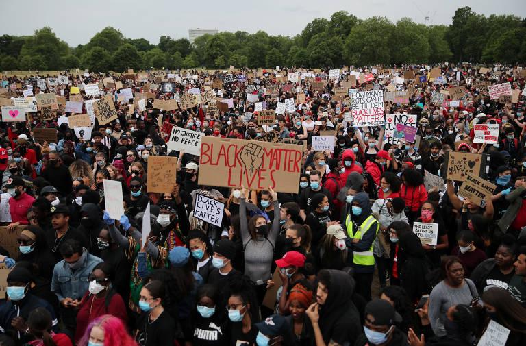 Muitas pessoas, quase todas de máscaras, estão em um gramado; algumas levam cartazes com palavras de ordem