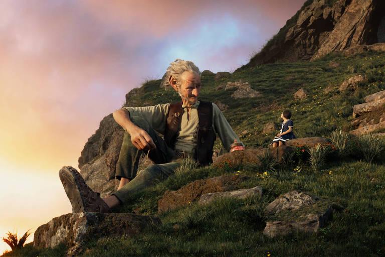 O gigante de cabelos brancos está sentado em uma colina com uma garota, os dois conversam sob o sol