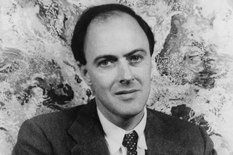 Roald Dahl está de terno e gravata e sorri de leve para a câmera