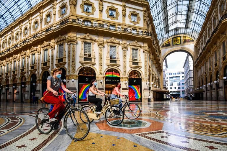 Três mulheres com máscara e andando em bicicletas passam por interior de prédio