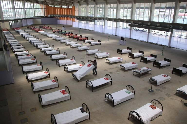 Espaço grande e aberto com quatro fileiras de camas; um homem está levantando uma das camas