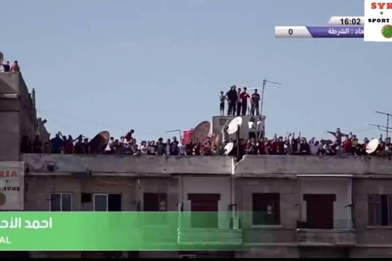 Torcedores do Al Ittihad Aleppo assistem a jogo do Campeonato Sírio em terraços e janelas de prédios para driblar proibição de público nos estádios