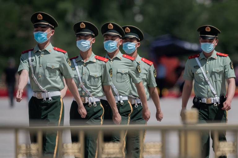 Cinco homens fardados e de máscara marcham em fila