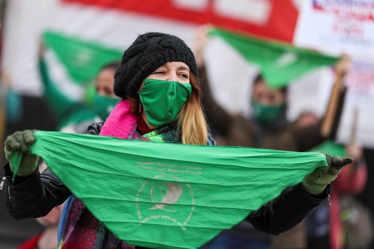 Manifestante com máscara protesta com lenço verde, símbolo do movimento pró-aborto, em ato em Buenos Aires