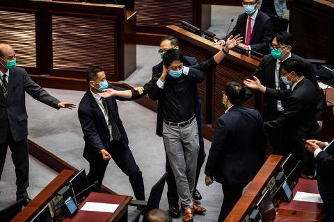 Pro-democracy legislator Ted Hui (C) is removed by security guards after throwing a jar containing a four-smelling liquid onto the floor during a debate on a law that bans insulting China's national anthem, at a session of the Legislative Council (Legco) in Hong Kong on June 4, 2020. - Hong Kong's legislature voted for a Beijing-backed law banning insults to China's national anthem on June 4, a move critics say further stifles dissent in the restless semi-autonomous financial hub. (Photo by ISAAC LAWRENCE / AFP) ORG XMIT: IL001