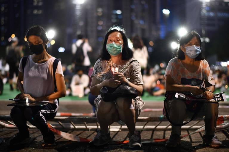 Manifestantes sobre grade derrubada no parque Victoria, em Hong Kong