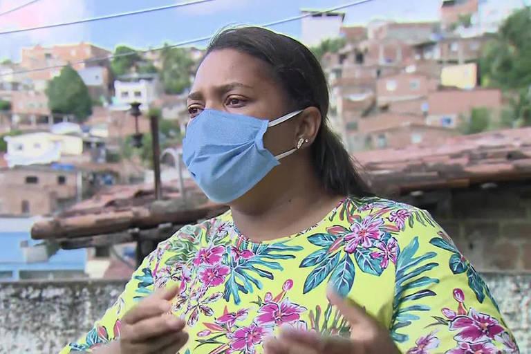Mirtes Renata Souza, mãe do menino Miguel Otávio, de 5 anos, que morreu ao cair de um prédio de luxo no centro do Recife; ela usa máscara azul e blusa estampada; ao fundo vê-se um morro com um casario simples, muitas casas sem acabamento