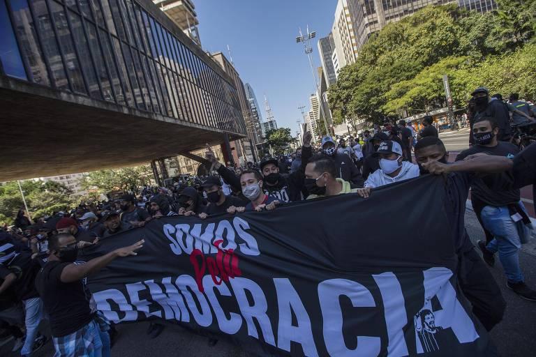"""Integrantes de torcidas organizadas diante do prédio do MASP com cartaz """"somo pela democracia"""""""