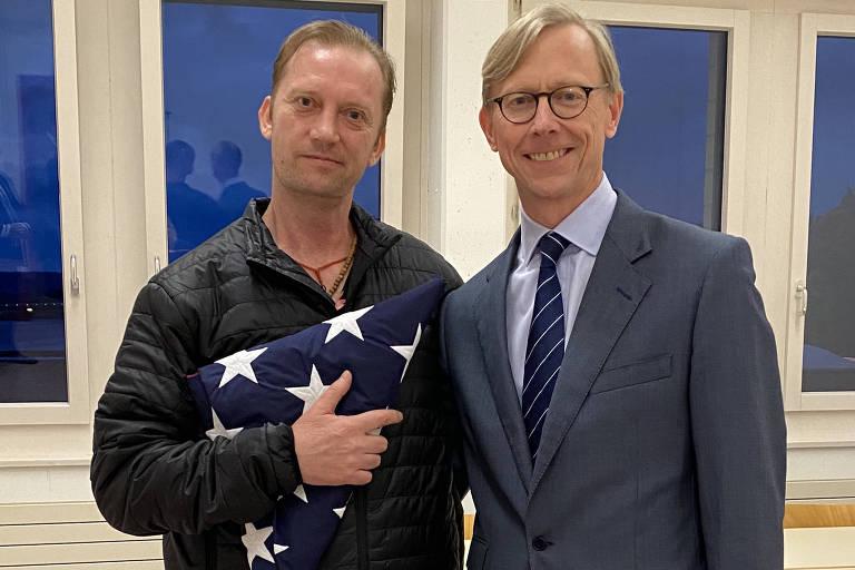 O veterano da Marinha dos EUA Michael White (esq.) posa ao lado do enviado especial americano ao Irã, Brian Hook, no aeroporto de Zurique, na Suíça