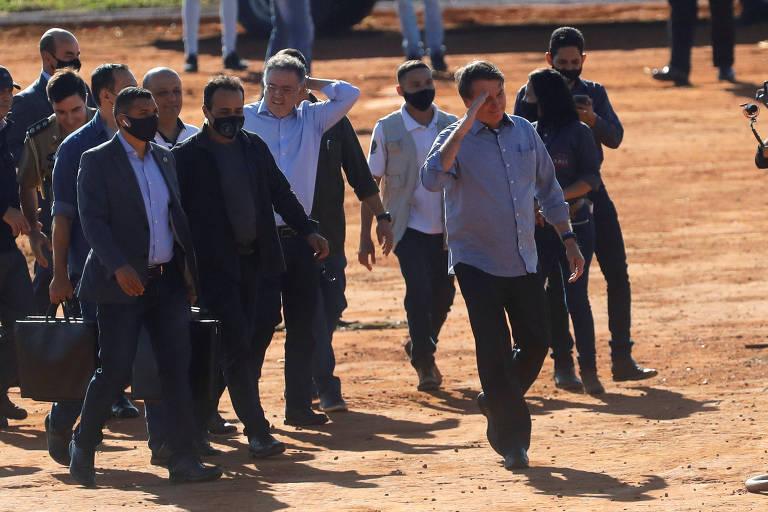 Presidente Jair Bolsonaro chega, sem máscara, à inauguração de um hospital de campanha para vítimas do novo coronavírus, ele está acompanhado de cerca de pessoas no fundo da foto. O chão é de terra batida.