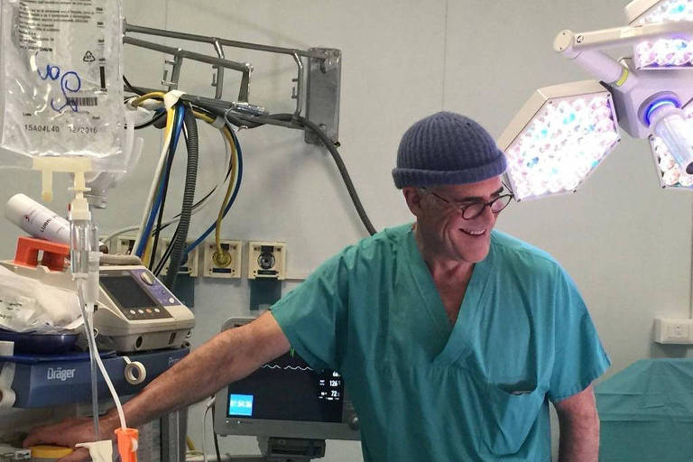 Médico de gorro e uniforme sorri em ambiente de sala de cirurgia