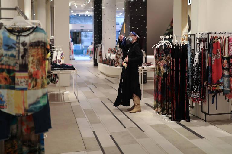 Mulher usa equipamentos de proteção durante visita a loja de Barcelona