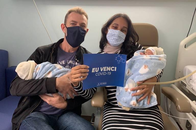 Mãe e pai carregam bebês gêmeos com placa que diz Eu venci a Covid