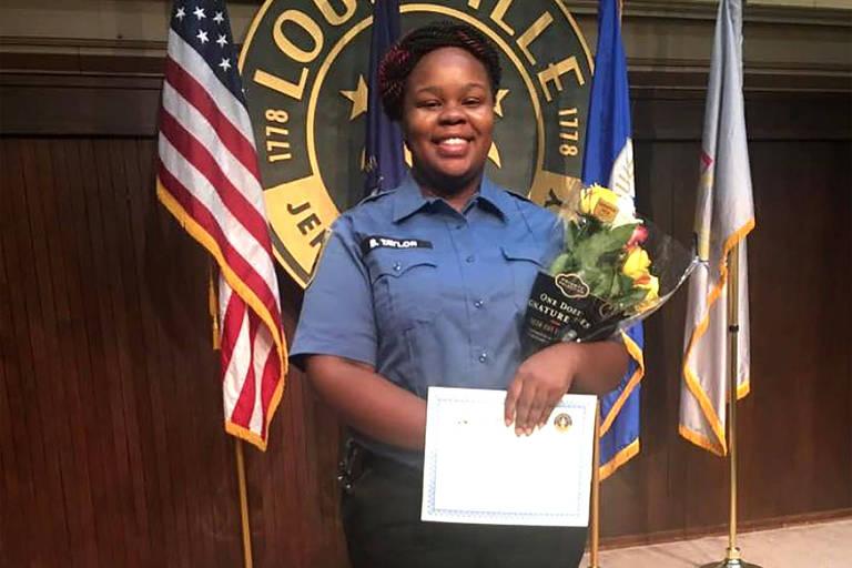 De uniforme e carregando flores e um diploma, Breoona Taylor posa para foto na sua cerimônia de graduação como paramédica, em Louisville, Kentucky