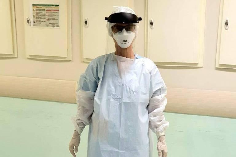Médica paramentada com avental e máscara em corredor de hospital