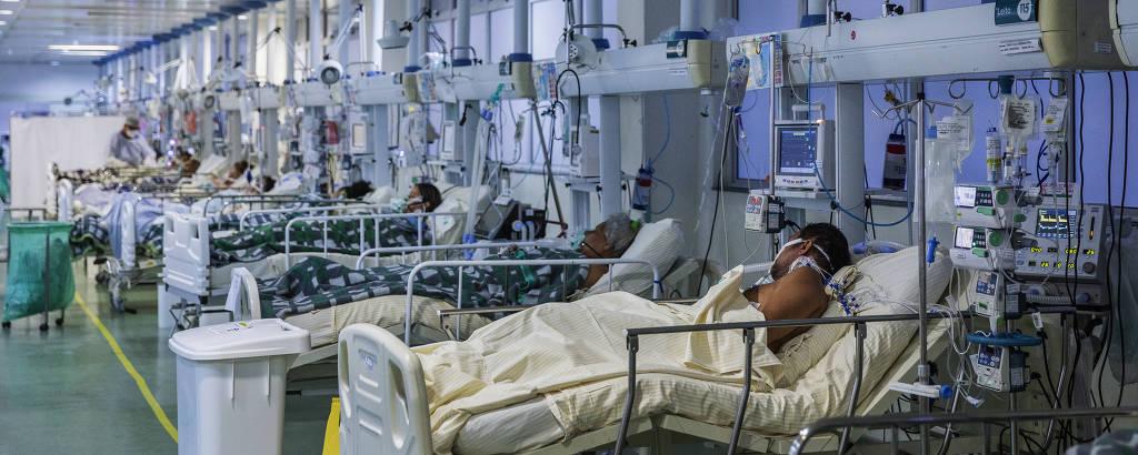 Pacientes com Covid-19 na Unidade de Terapia Intensiva do Hospital Municipal Moyses Deutsch ( M'Boi Mirim ); vemos um ambiente com paredes azuladas, um corredor amplo, visto em perspectiva, ao longo do qual há vários leitos, um ao lado do outro, com aparelhagens vindas do teto