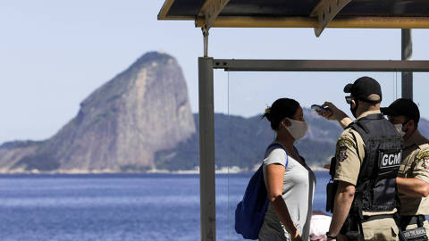 Agents check the temperature of a woman wearing a protective mask after she got off a public bus, with Sugar Loaf mountain on backgorund, at Niteroi city during its first day of lockdown, as the spread of the coronavirus disease (COVID-19) continues, near Rio de Janeiro, Brazil, May 11, 2020. REUTERS/Ricardo Moraes ORG XMIT: GGGRJO15