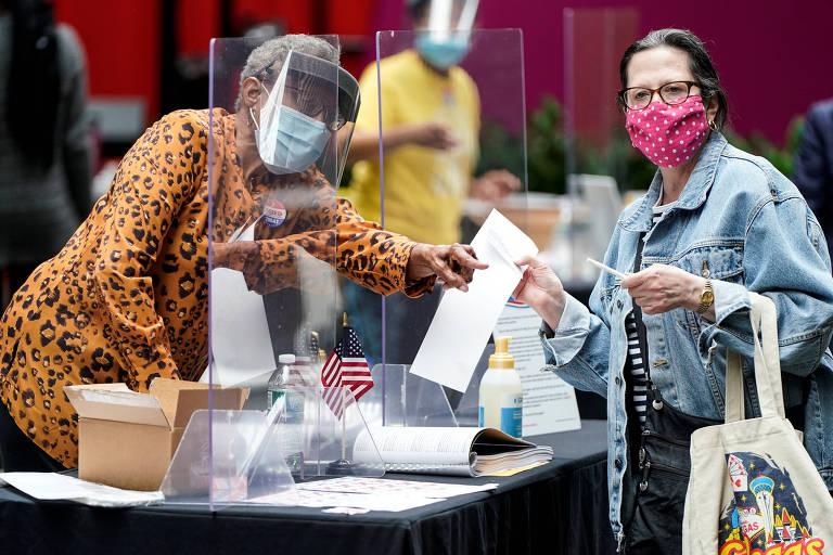 Mesário usando proteção facial para evitar transmissão do novo coronavírus entrega cédula a eleitora nas primárias da Filadélfia (EUA)