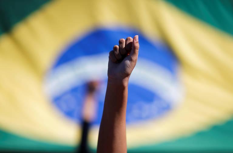 Manifestante levanta o punho na frente de uma bandeira do Brasil.