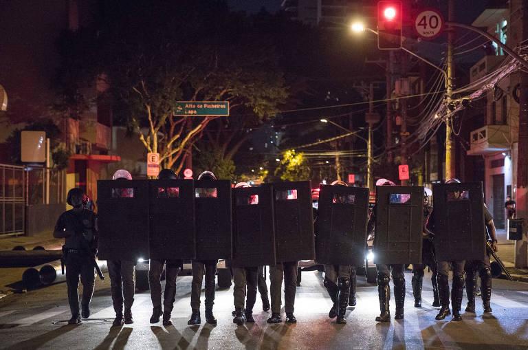 Policiais com escudos diante do corpo no meio de uma rua à noite