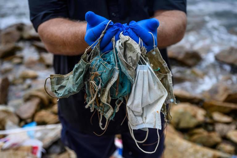 Ativista mostra máscaras descartadas recolhidas em uma praia na área residencial de Discovery Bay, em Hong Kong