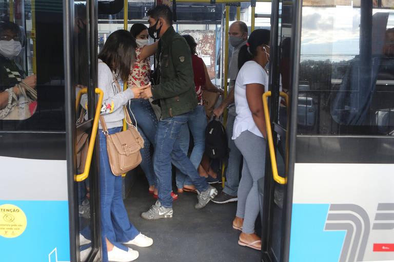 Passageiro em pé na porta do ônibus na Parada Rio Bonito